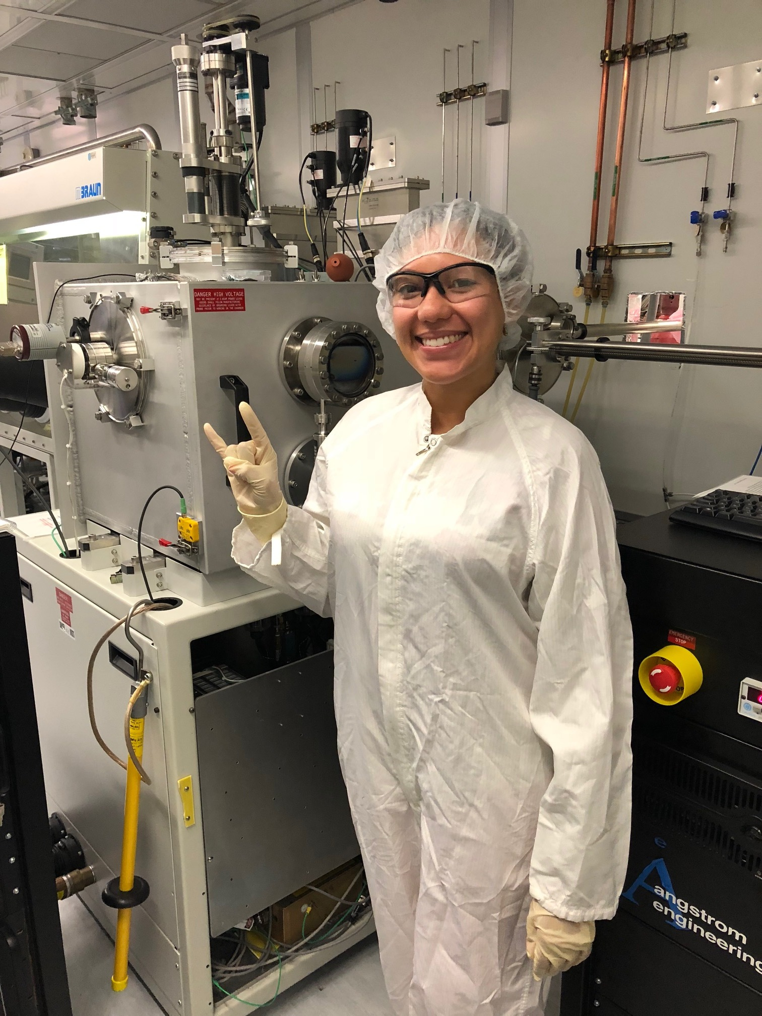 Wendilyn Ilund, a previous RET at UT, stands in her summer laboratory. She is wearing personal protective gear including safety goggles and gloves.